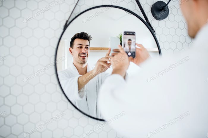 Young man in the bathroom in the morning, taking selfie