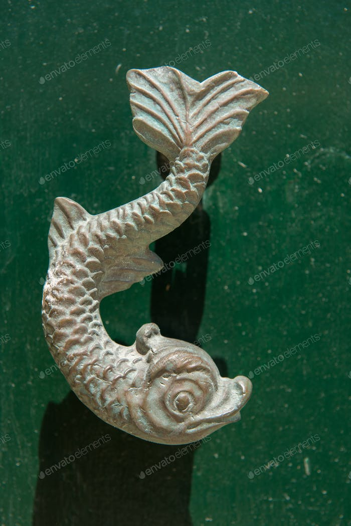 Close-up view of the fish shaped knocker on a green wooden door. Valetta, Malta