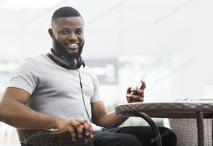 Handsome african man sitting in cafe and waiting for order
