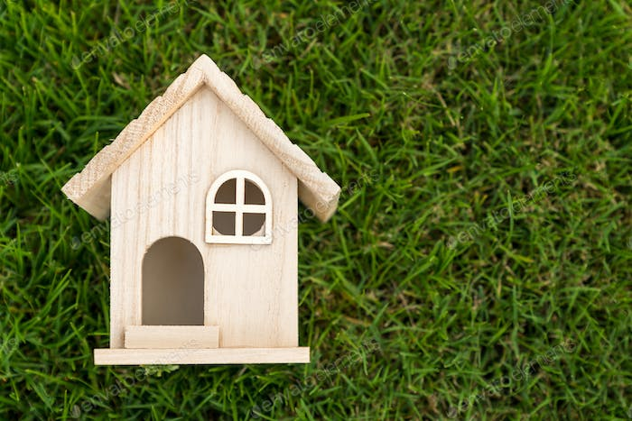 Flat lay view of little wooden house on green grass
