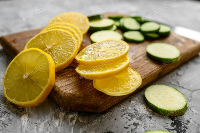 Cutted lemon and cucumber on grunge background