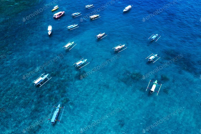Boats in the blue lagoon. Aerial view of floating boat on transparent turquoise water at sunny day.