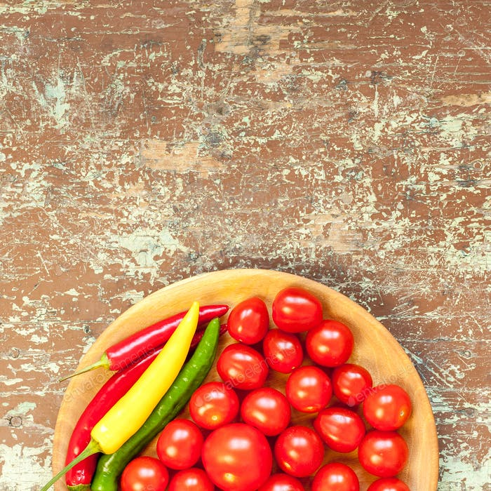 Fresh home grown vegetables in a bowl on wooden background