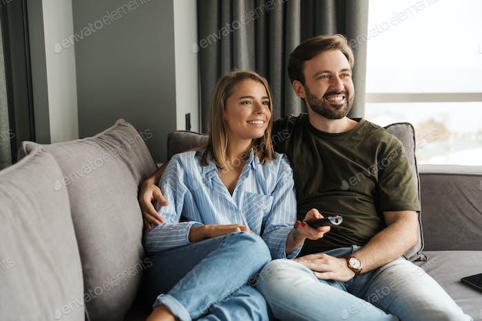 Foto des freudigen Paares Fernsehen und mit Fernbedienung