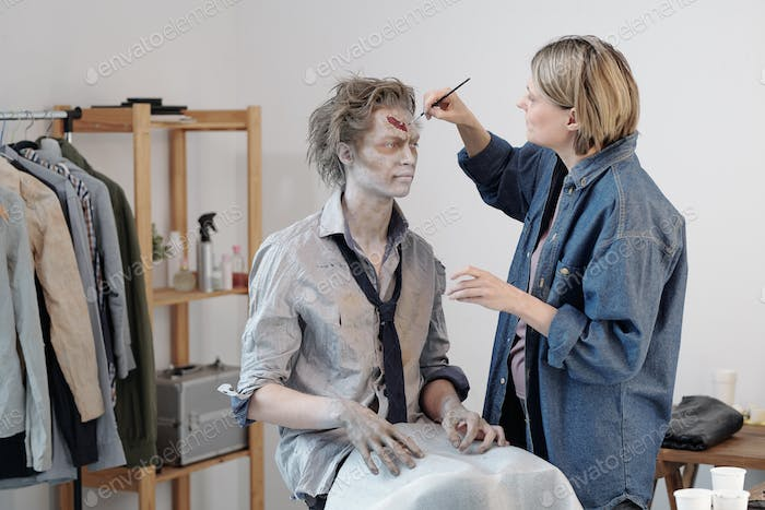 Contemporary female visage artist with brush applying zombie greasepaint on forehead of young man