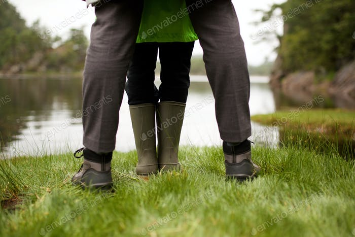 behind of legs with boots standing by lakeside