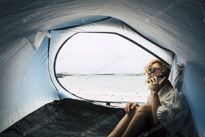 cheerful traveler lady with curly hair in the wind write on smartphone