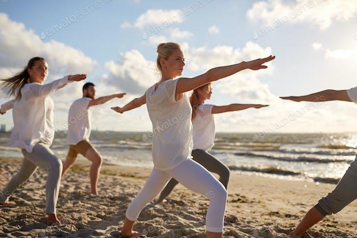 Gruppe von Menschen, die Yoga-Übungen am Strand machen