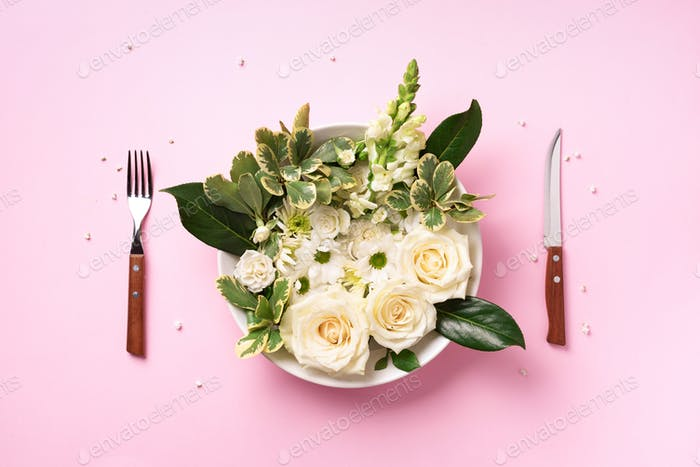White flowers on plate, fork, knife over pastel pink background. Healthy eating, vegan diet concept
