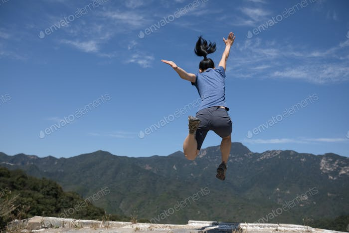 hipster woman jumping on top of great wall in china