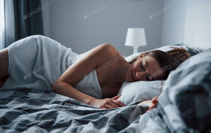 Auf der linken Körperseite. Hübsche junge Frau liegt morgens auf dem Bett in ihrem Zimmer