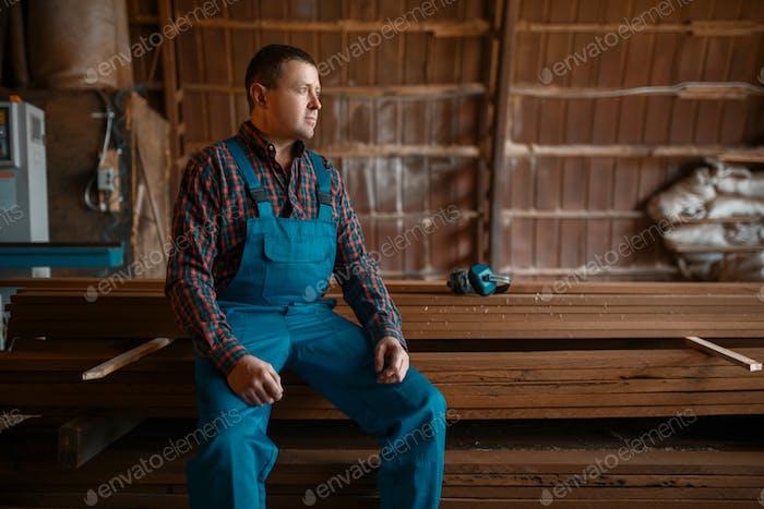 Tischler in Uniform am Arbeitsplatz auf Holzmühle