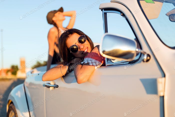 Two pretty young women driving on road trip on beautiful summer