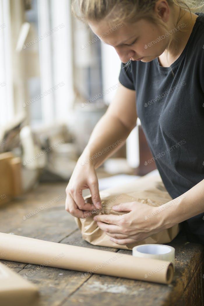 Frau stehend in einer Werkstatt Versiegelung einer Verpackung in braunem Verpackungspapier mit Klebeband eingewickelt.