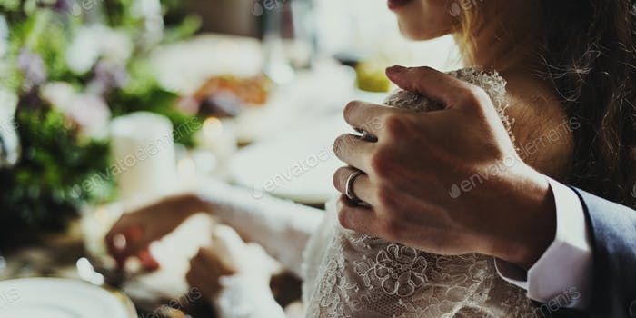Groom Hand Holding Bride Closely on Wedding Reception