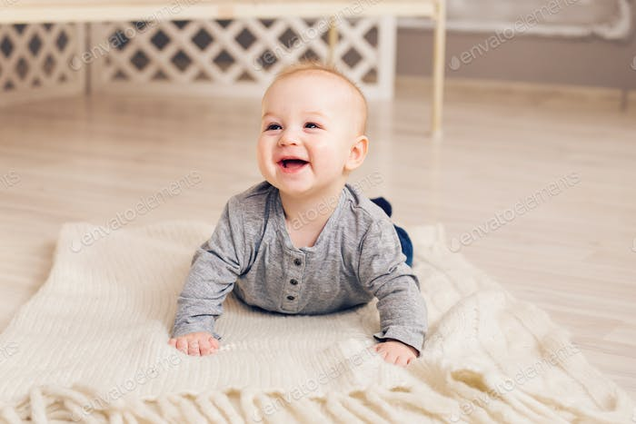 Adorable laughing baby boy in white sunny bedroom. Newborn child relaxing. Family morning at home.