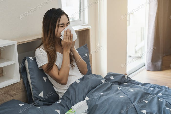 Asian woman feeling unwell and sneezing on the bed