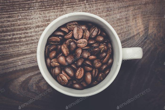 Tasse Kaffeebohnen auf braunem Holzhintergrund