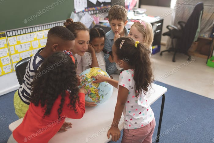 High angle view of a teacher and school kids interacting about a earth globe in classroom