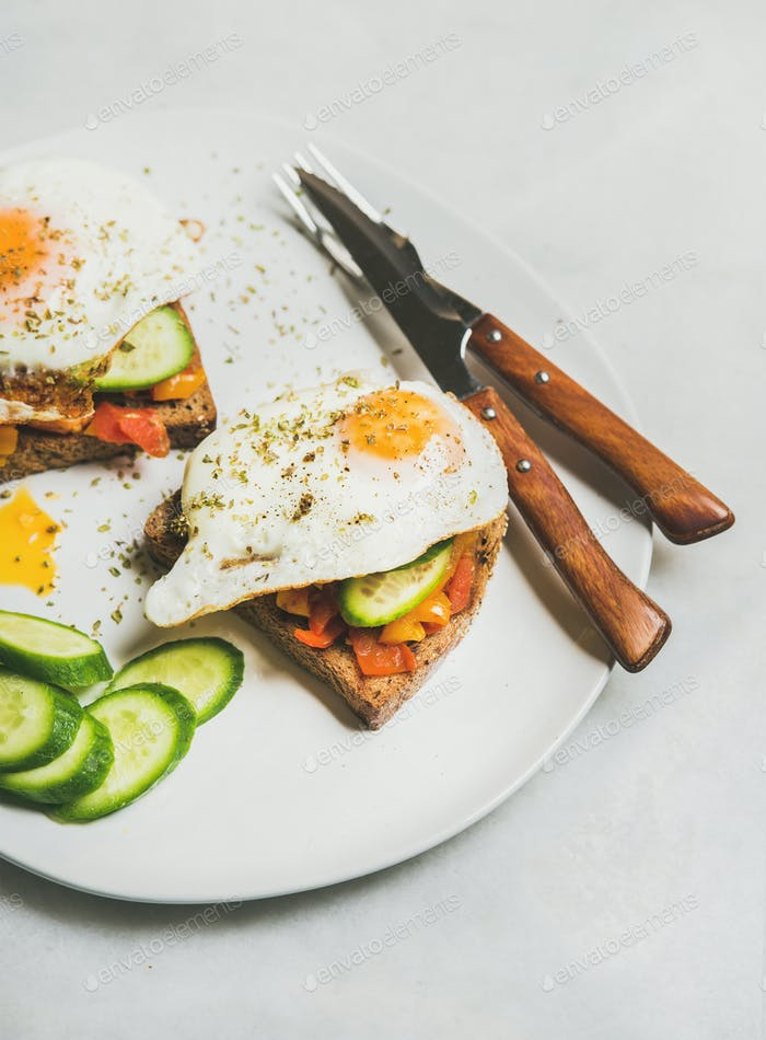 Breakfast toast with vegetables and fried egg on white plate