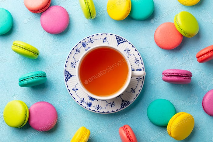 Macaroons Dessert and Cup of Tea on Blue Background. Flat Lay Composition. Top view.