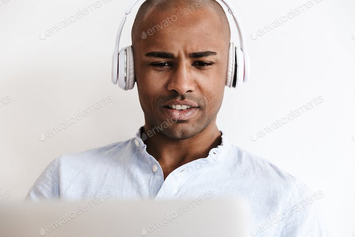 Photo of bald african american man in headphones working with laptop
