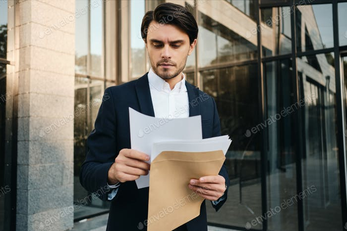 Young businessman standing outdoor thoughtfully reading documents with glass building on background
