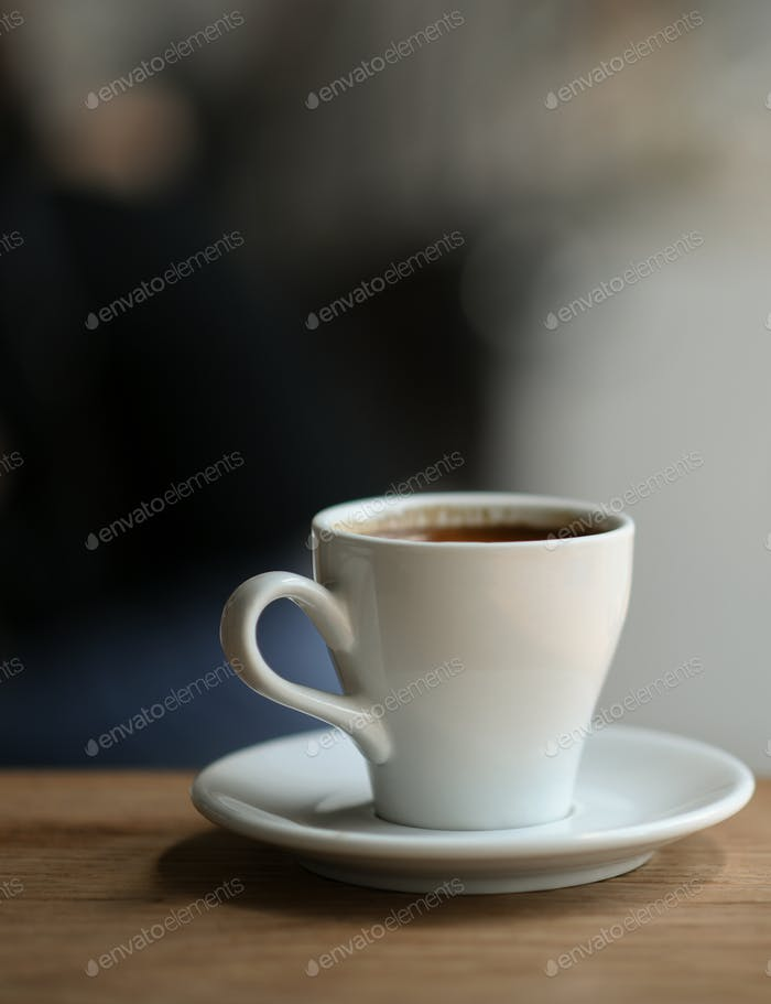 Coffee in white mug on a wooden floor, Close-up vertical image.
