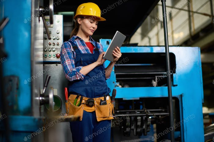 Female Technician Working at Factory