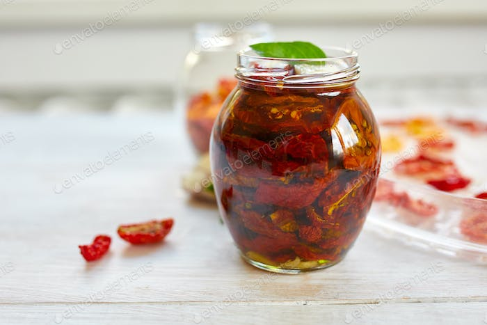 Homemade sun dried tomatoes with herbs, garlic in olive oil in a glass jar