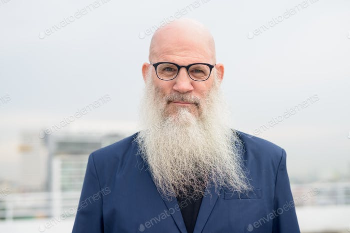 Face of mature bald bearded businessman with eyeglasses against view of the city