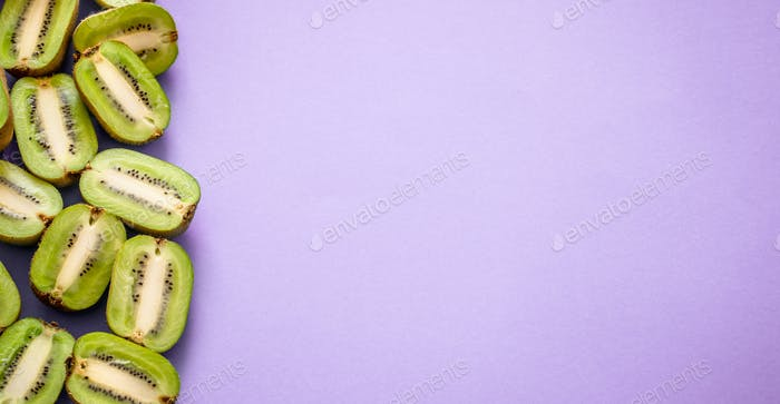 Mitades frescas de kiwi sobre un fondo púrpura