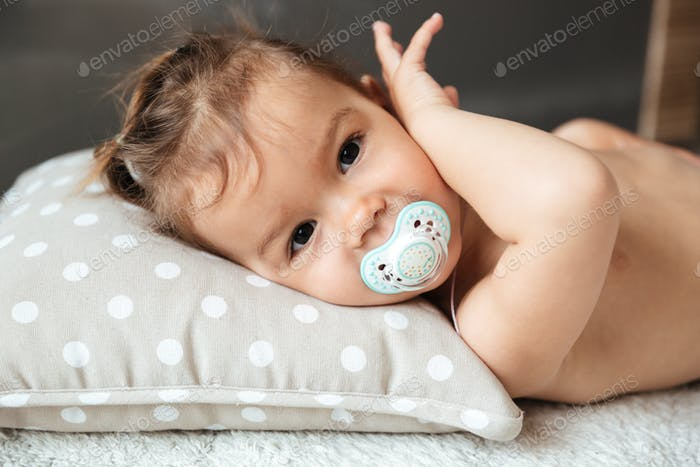 Cute little girl child indoors with nipple lies on bed.