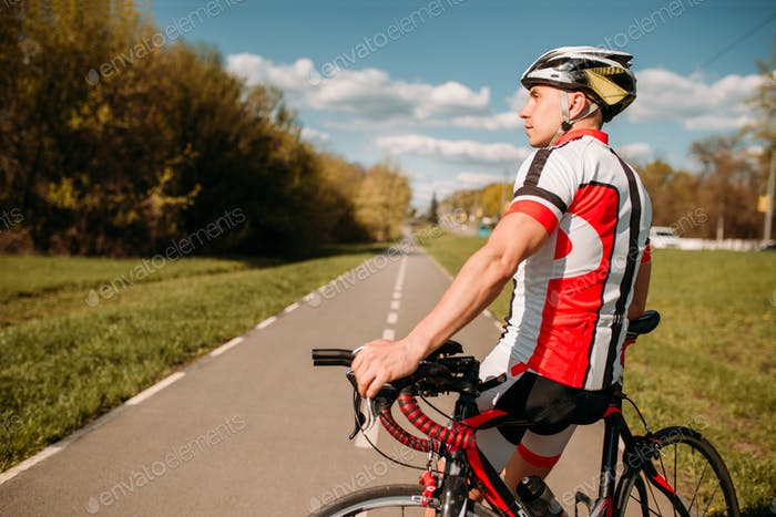 Cyclist in sportswear, cycling on asphalt road