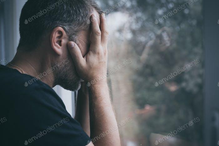 Porträt ein trauriger Mann stehend in der Nähe eines Fensters