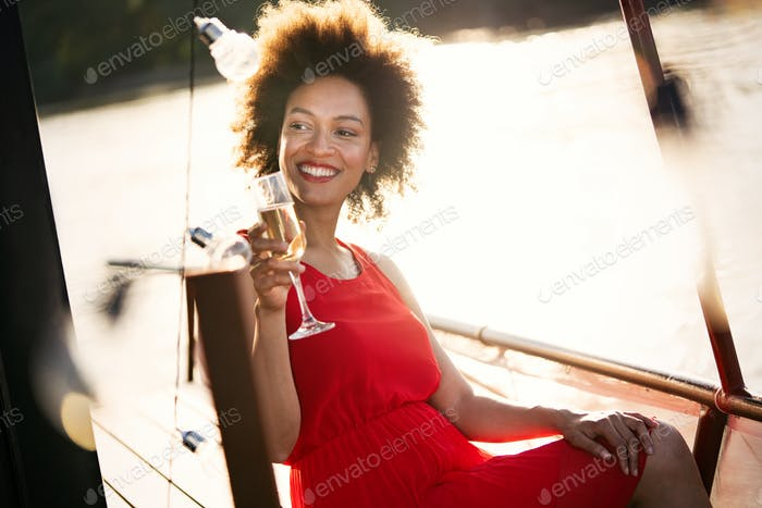 Lifestyle fashion portrait of stunning woman resting outdoor. Glass in hand. Drinking champagne