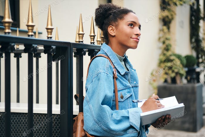 African American student girl in denim jacket with backpack dreamily writing notes on city street