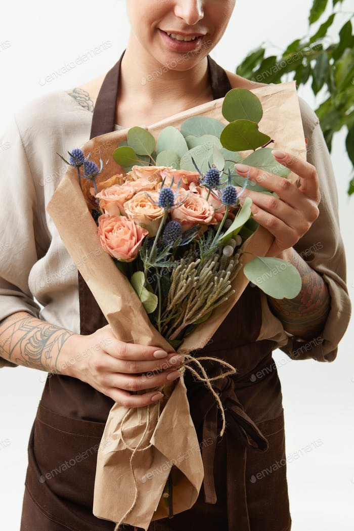 Smilling girl florist with creative bouquet from fresh flowers roses in a paper on a light