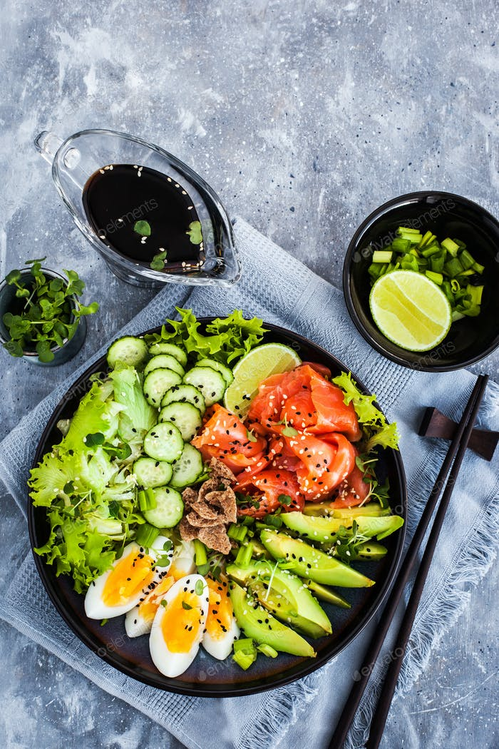Salmon poke bowl served with avocado, eggs, cucumber and greens