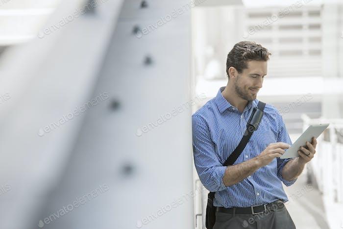 Ein Mann in Hemd und Krawatte mit einem Handheld-Digital-Tablet in einer urbanen Szene.