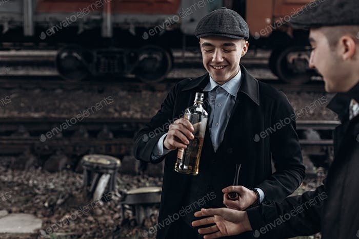 Brutal gangsters drinking  on background of railway carriage