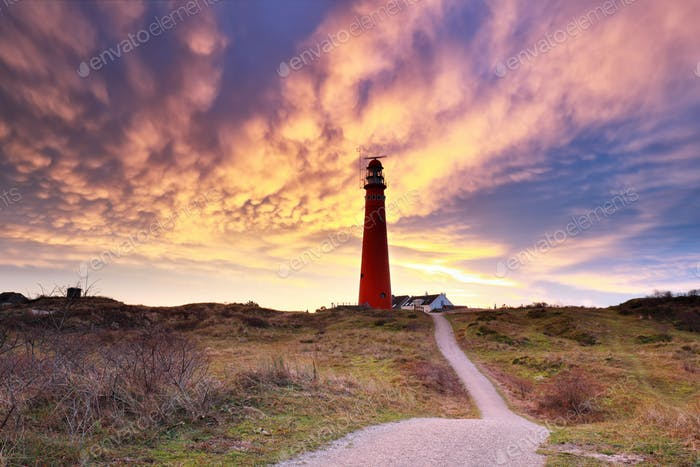 dramatic mammatus clouds over red lighthouse