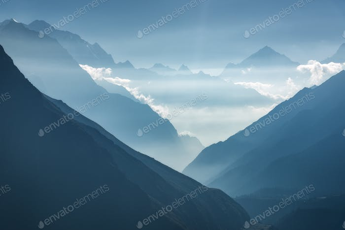 Majestic view of silhouettes of mountains and low clouds at sunset