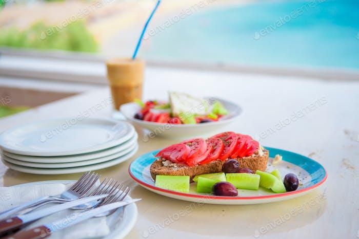 Traditionelles Mittagessen mit leckerem frischen griechischen Salat, Frappe und Brusketa zum Mittagessen im Freien
