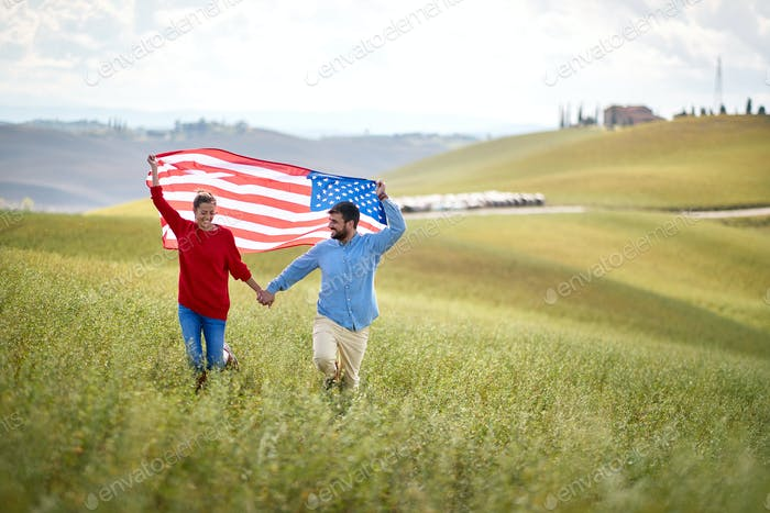 couple at meadow with American flag . Election, campaign, freedom