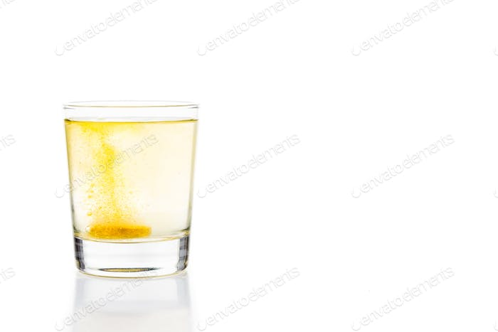 Effervescent vitamin C tablet dissolving in a glass of water