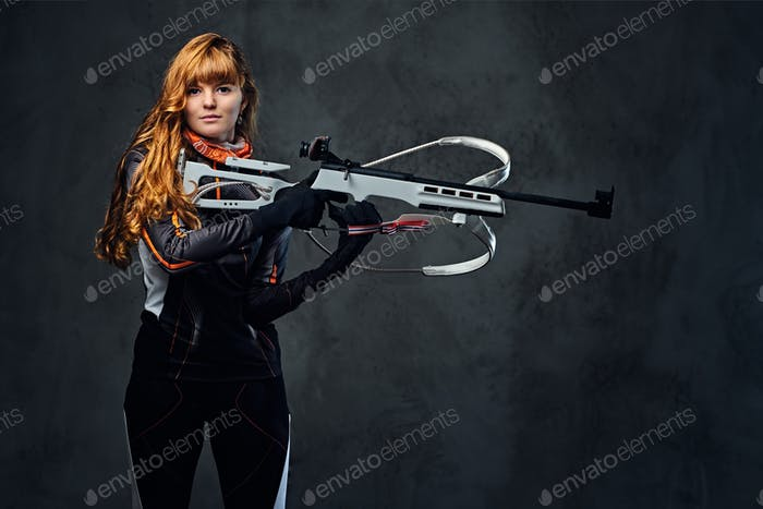 Redhead female Biathlon champion aiming with a competitive gun.