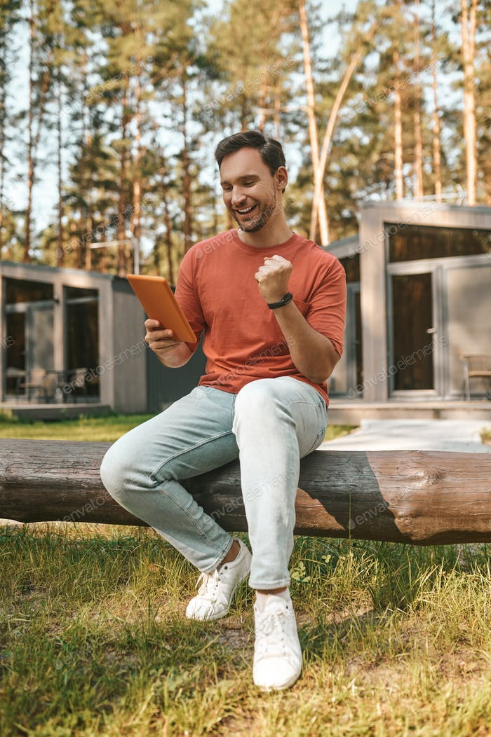 Enthusiastic man with tablet sitting in nature