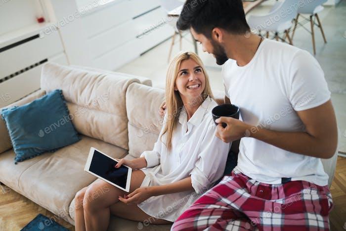 Glückliches Paar in der Liebe mit Tablet in Pyjamas