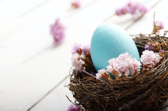 Rustic style painted easter egg in the nest on white table